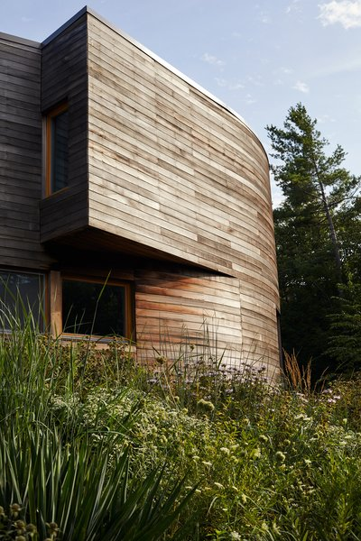 The cedar-wrapped house, designed by BriggsKnowles A+D, is gently curved at the center.