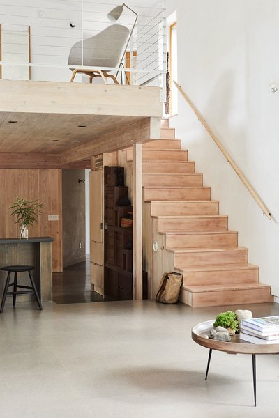 In the living room, cork flooring meets a fir staircase. The lofted family room features a chair from the Danish Design Store and a Grasshopper floor lamp by Greta Grossman for Gubi.