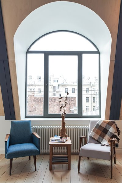 A pair of vintage chairs and an IKEA side table provide a cozy place to sit in Vladimir Samsonov and Alya Shipilova's St. Petersburg pied-à-terre.