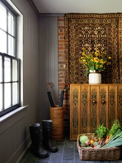 The enlarged mudroom benefits from honed, gray slate floor tiles and newly painted beadboard on the walls. A midcentury Danish cabinet from a local antique shop pairs with an antique rug hung behind it.
