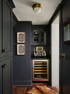Previously, this quirky space had a pantry, broom closet, and doors leading to the basement. Now, this niche houses a butler's pantry with a custom dry bar, wine fridge, and storage cabinets awash in Farrow & Ball Studio Green with a Soapstone countertop.