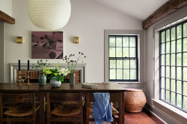 The architects removed decorative wood beams and wood paneling, and raised the ceiling to reveal a bright, open space. The existing fireplace mantle was swapped out for Bolection molding, a minimal-yet-traditional profile that allows more space for wall art. Hendricks installed the sconces and Noguchi lantern above the clients' wood table and chairs.