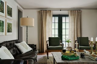 The home's small footprint inspired Hendricks to choose a minimal paint palette featuring two shades of Farrow & ball white used throughout the first floor. A mix of midcentury pieces sourced from local antique shops sits against a canvas of custom linen curtains. A Brazilian leather sofa adds a sumptuous touch, and the rosewood chairs are upholstered in a serene, olive-green fabric.