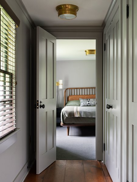 The pine ceiling was removed, and wall-to-wall carpeting installed underneath a Rejuvenation bed. A former built-in home office in the adjacent hallway was retrofitted to accommodate a row of closets.
