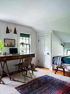 The clients' request for a more flexible space that could accommodate guests and a home office was met by removing the wall and building closets in each corner. The original space featured a sloped ceiling, which was preserved, while two custom day beds make room for a centered desk and chair.