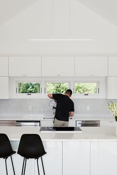 The kitchen features LG quartz countertops, appliances by KitchenAid, and molded plastic stools by Charles and Ray Eames from Design Within Reach.