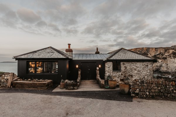 When renovating a centuries-old beach cottage in Cornwall, architect Adam Casey of Watershedd covered one of the existing additions in vertical black timber.