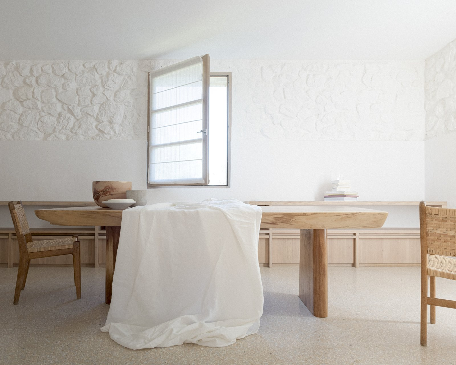 Dining Room, Chair, Storage, Table, and Shelves Solid oak, built-in shelving in the living and dining area keeps things streamlined.  Photo 5 of 14 in An Architect Turns a Weathered French Farmhouse Into a Monastic Retreat for His Parents