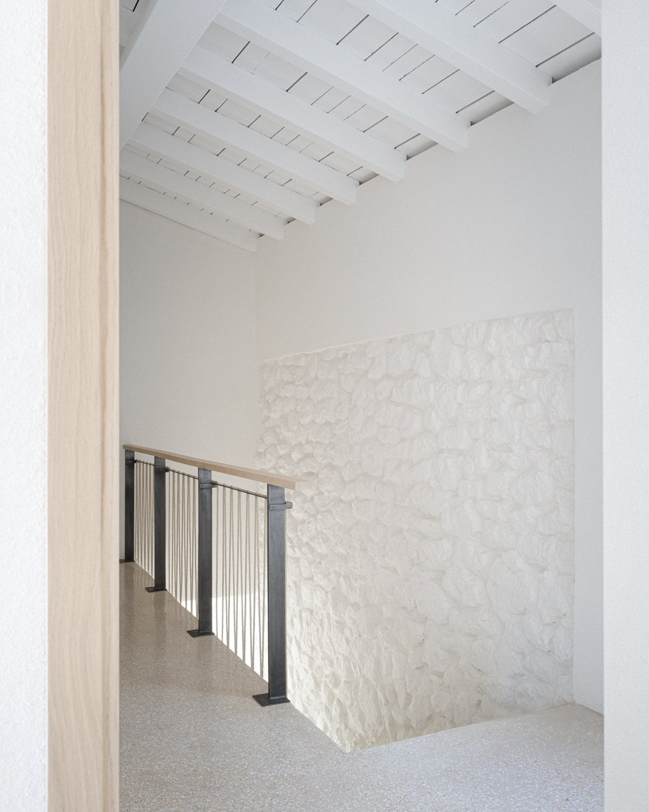 Hallway Subtly textured plaster walls meet hand-cut stone, creating a natural and organic feel.  Photo 8 of 14 in An Architect Turns a Weathered French Farmhouse Into a Monastic Retreat for His Parents