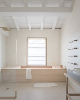VOLA towel-warming rails climb the wall next to a custom-designed soaking tub crafted in Japan out of hinoki wood, or Japanese cypress.
