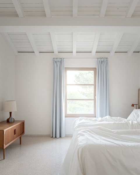 Exposed beams and rafters crown the guest bedroom.