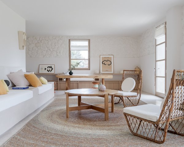 In the living area, a pair of rattan chairs found at the Paul Bert flea market in Paris join a coffee table designed by Guillerme et Chambron, also a flea-market find. A custom rug by CODIMAT was made in Madagascar.