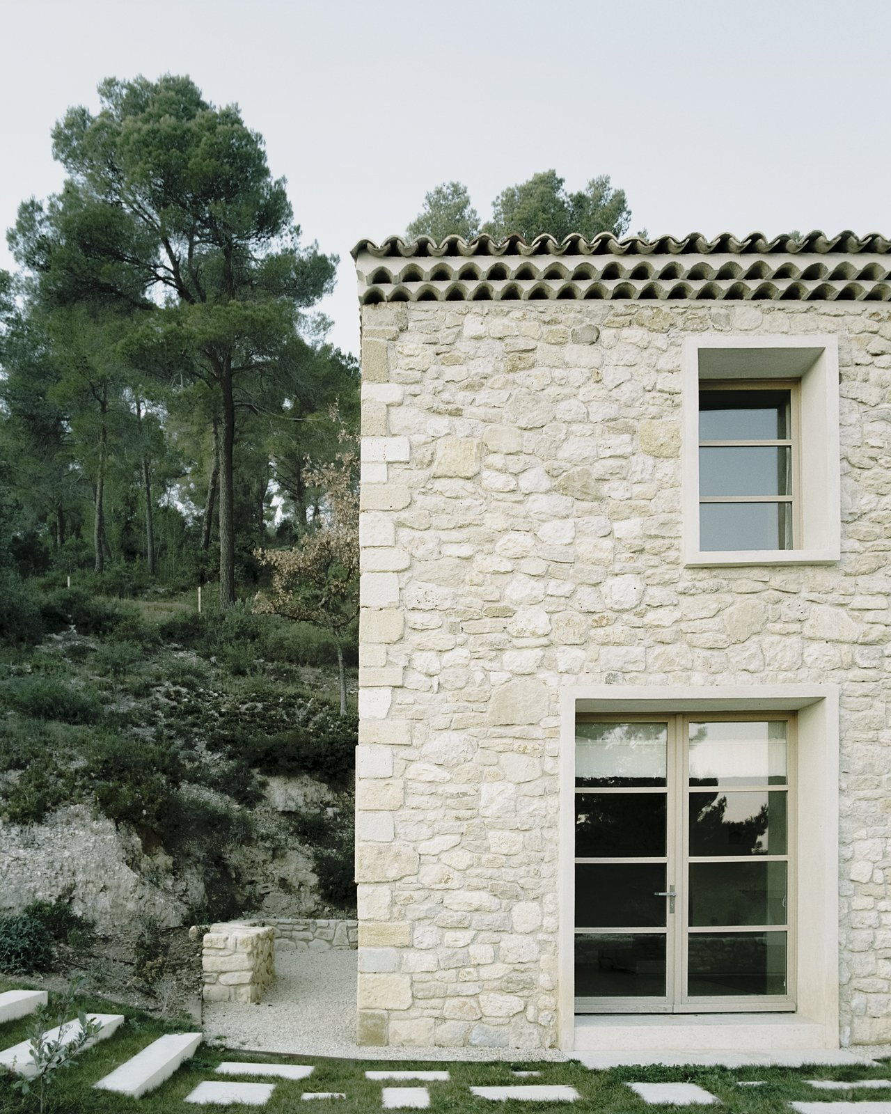 """Exterior, House Building Type, Farmhouse Building Type, Stone Siding Material, and Flat RoofLine """"15% of those stones are from the original house,"""" says Timothee. """"We dismantled the existing structure looking out for those rare elements, which were then added to the masonry once the foundations were poured.""""  Photo 2 of 14 in An Architect Turns a Weathered French Farmhouse Into a Monastic Retreat for His Parents"""