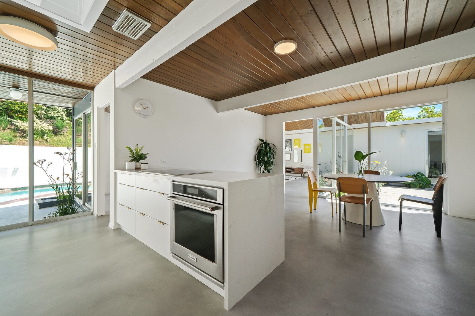 Floor-to-ceiling windows usher in an abundance of light into the 2,421-square-foot interior, while enhancing the home's intimate indoor-outdoor connection.  Photo 14 of 22 in Before & After: Another A. Quincy Jones Eichler Is Returned to its Former Glory in Oakland