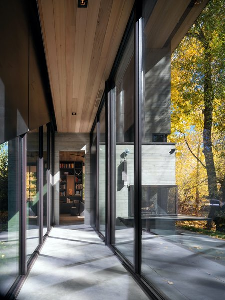 Dual-sided floor-to-ceiling glazing in the central interior walkway lends the sense that one is walking through the natural landscape, even inside the home.