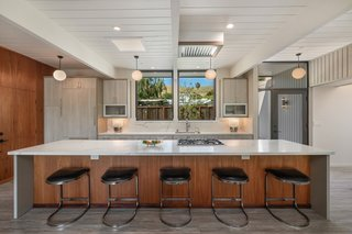 Kitchen, Engineered Quartz Counter, Vinyl Floor, Ceiling Lighting, White Cabinet, Pendant Lighting, Stone Slab Backsplashe, and Undermount Sink A 14-foot-long island topped with quartz offers bar seating in the kitchen. Light wood cabinetry and built-in Gaggenau appliances round out the space.