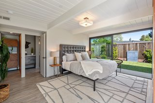 Bedroom, Lamps, Bed, Night Stands, Vinyl Floor, and Ceiling Lighting A look at the master suite, which includes an expansive sliding door that opens to the side yard. The master bathroom features Italian Carrara marble counters and a rain shower.
