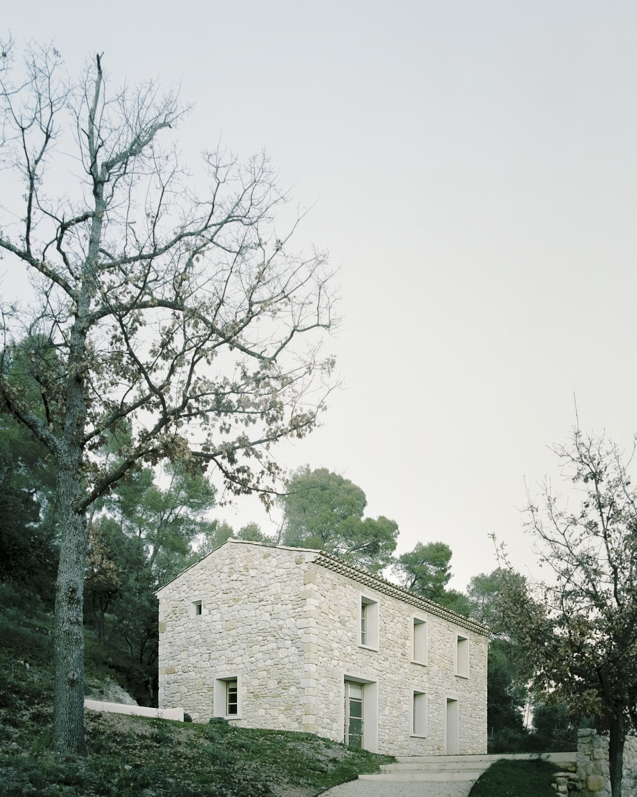 Exterior, House Building Type, Gable RoofLine, Farmhouse Building Type, and Stone Siding Material Architect Timothee Mercier of Studio XM converted a crumbling farmhouse into a residence for his parents.  Photo 1 of 14 in An Architect Turns a Weathered French Farmhouse Into a Monastic Retreat for His Parents