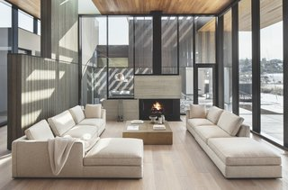 """Back inside, the glass-enclosed living room is grounded by a central fireplace. """"When we started designing this project, we always had cedar in mind,"""" says Corey. """"It wasn't like, 'Oh, it could be metal or oak. Instead, it was, 'this is a cedar box; we're carving it out.' """""""