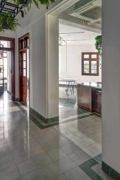 The existing terrazzo flooring serves as a guide through the space, emphasizing the locations of existing walls and selectively infilled with glass, like at this original opening in the corridor.