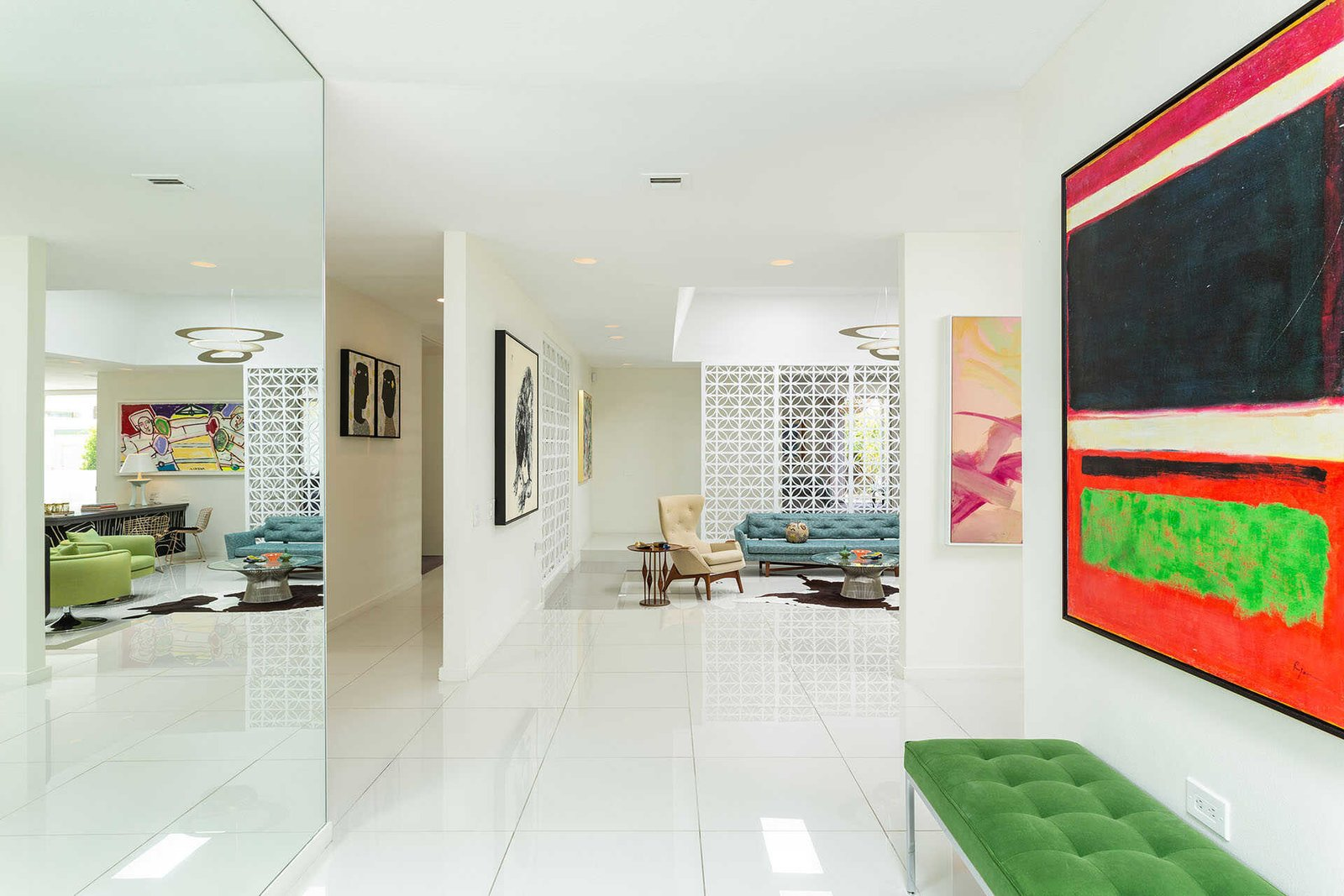 Designed for entertaining, the 3,848-square-foot residence offers an open floor plan with spacious living areas. White terrazzo floors complement the neutral palette while bright artwork infuses vibrant color throughout.  Photo 3 of 13 in A Sassy, Pink-Trimmed Ranch Near Palm Springs Lists for $899K