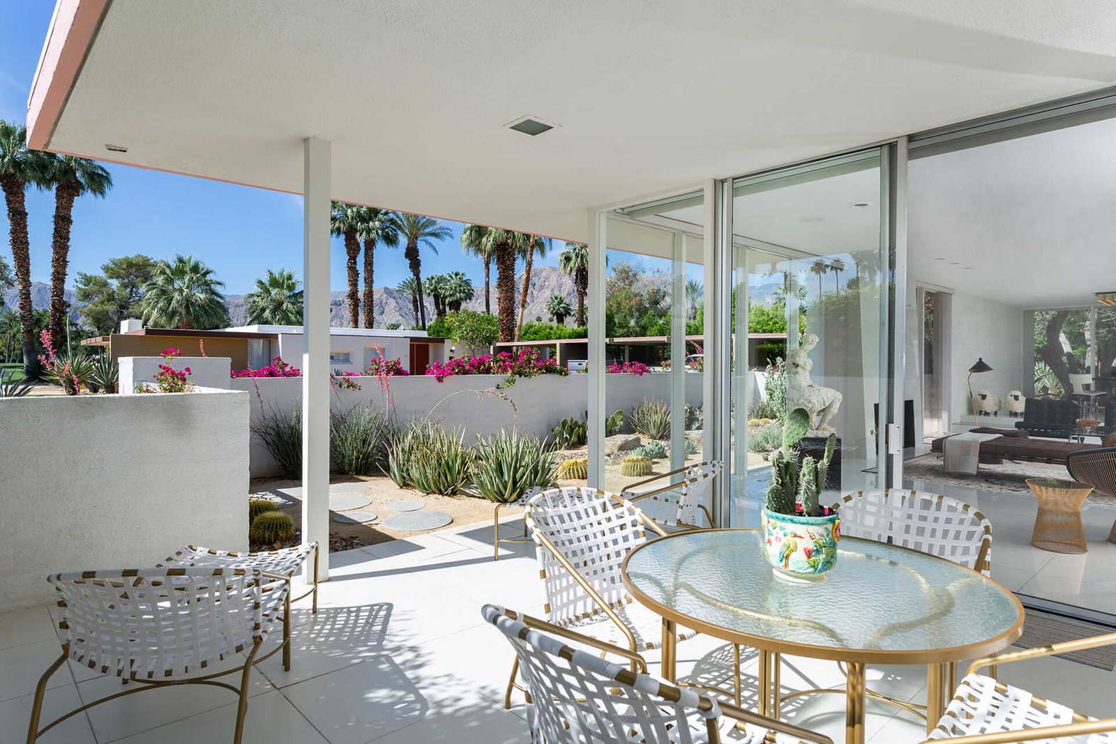 Off the living room is an expansive outdoor dining area created by the roof overhang.  Photo 9 of 13 in A Sassy, Pink-Trimmed Ranch Near Palm Springs Lists for $899K
