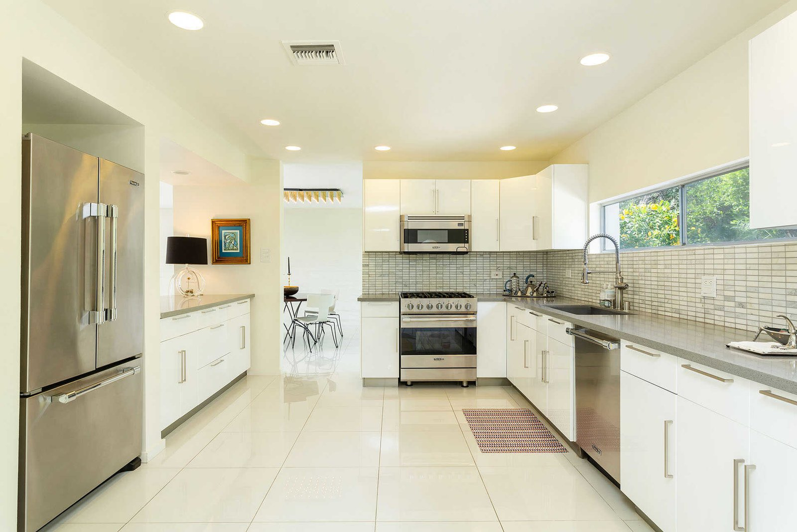 Clerestory windows invite natural light into the kitchen, which features custom cabinetry and Viking appliances.  Photo 7 of 13 in A Sassy, Pink-Trimmed Ranch Near Palm Springs Lists for $899K
