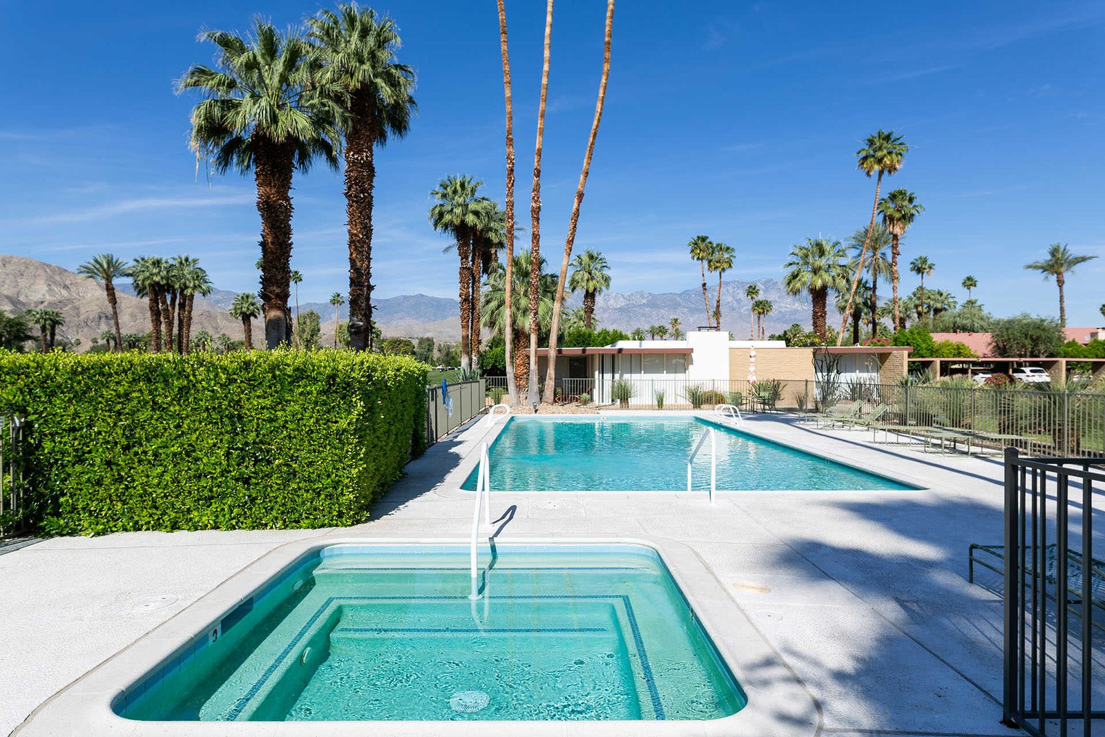 A large swimming pool and spa await in the backyard.  Photo 13 of 13 in A Sassy, Pink-Trimmed Ranch Near Palm Springs Lists for $899K