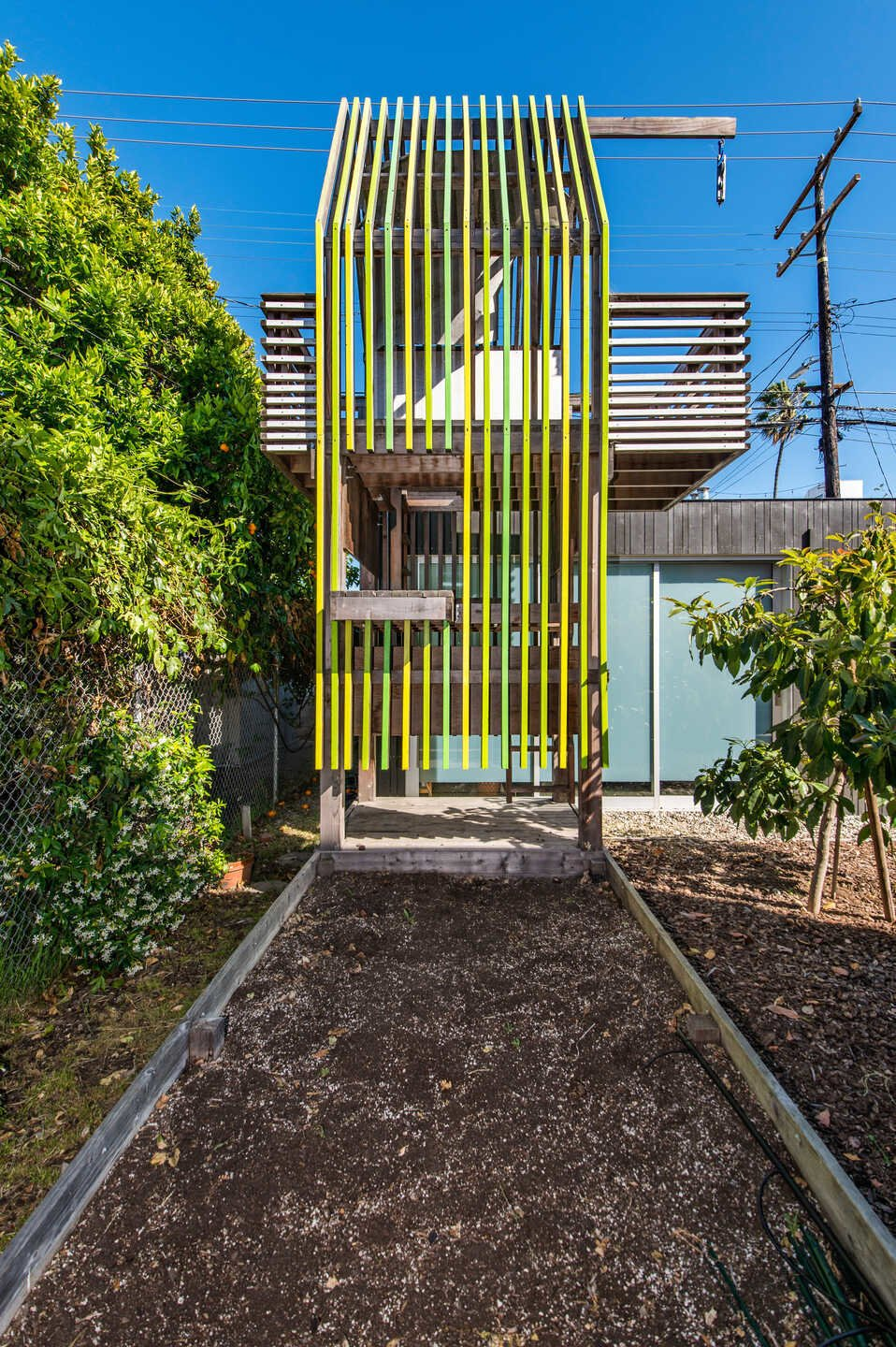 The whimsical play area awaits new owners. A detached, two-car garage sits just behind.  Photo 14 of 14 in This House With Larger-Than-Life California Poppies on Its Facade Just Hit the Market for $3.4M