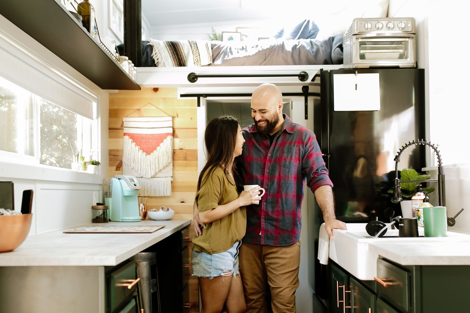 Saul and Trysh Martinez stand in the kitchen of the 250-square-foot home they built for themselves to escape mortgage and rent payments on top of their student loans.  Photo 1 of 13 in Budget Breakdown: Two Travel Therapists Build a Tiny Home-on-Wheels for $24K