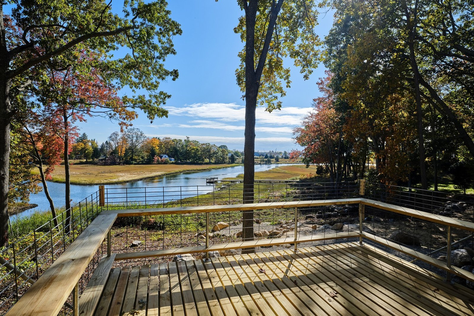 Outdoor, Small Patio, Porch, Deck, Woodland, Trees, Wood Patio, Porch, Deck, Grass, and Side Yard The view from the large deck at the back of the property.  Photo 9 of 10 in A Connecticut Condo That Hugs the Patchogue River Asks $575K