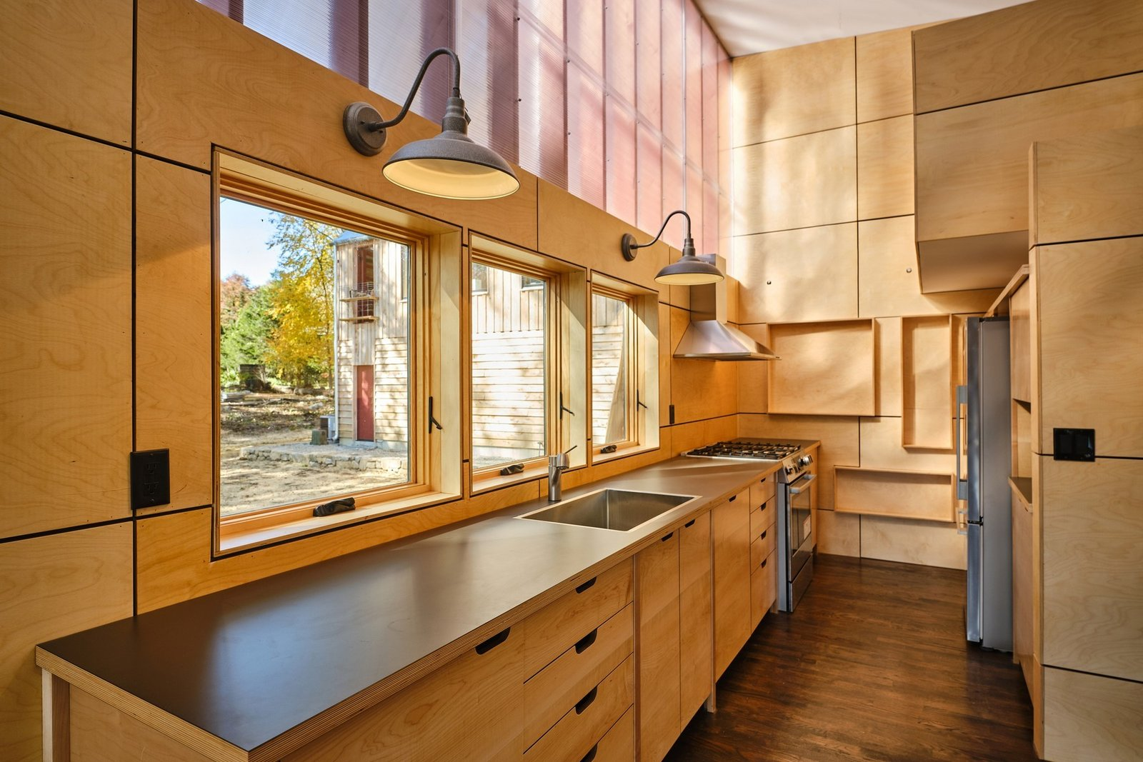 Kitchen, Wood Cabinet, Wall Lighting, Range, Range Hood, Drop In Sink, Dark Hardwood Floor, Wood Backsplashe, and Refrigerator The kitchen features all new stainless-steel appliances and custom cabinetry.  Photo 5 of 10 in A Connecticut Condo That Hugs the Patchogue River Asks $575K