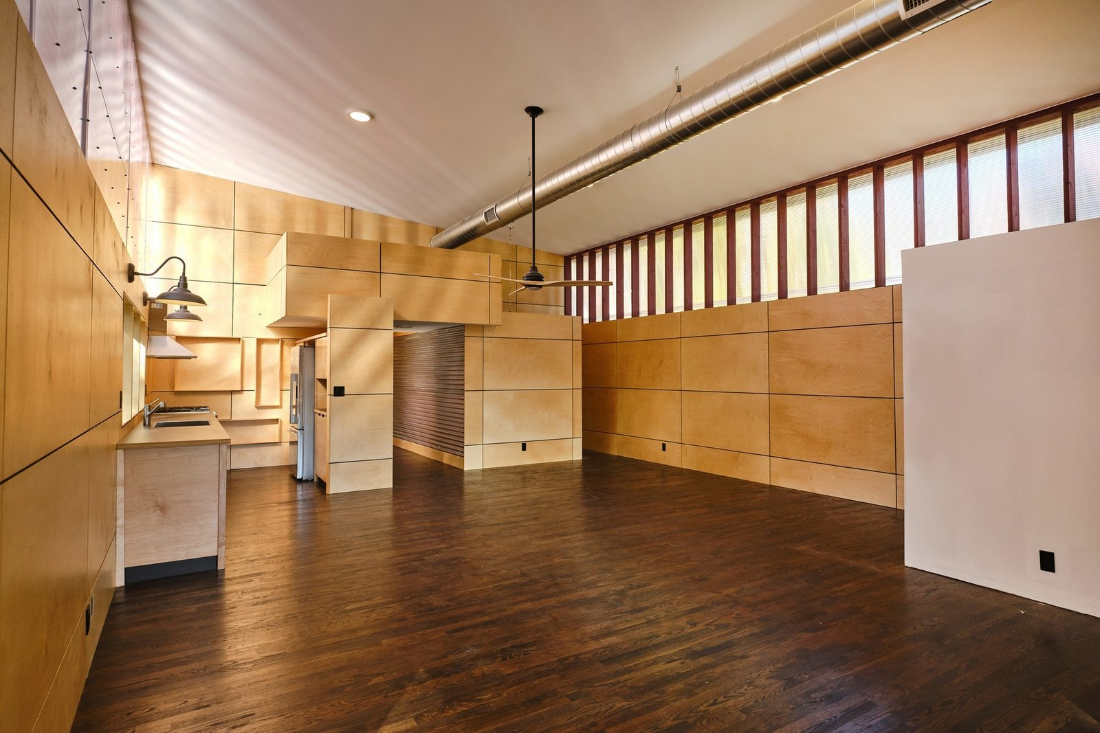 Living Room, Dark Hardwood Floor, and Ceiling Lighting Clerestory windows line one of the walls, further illuminating the space. Light Birch panels contrast with the dark hardwood floors.  Photo 4 of 10 in A Connecticut Condo That Hugs the Patchogue River Asks $575K