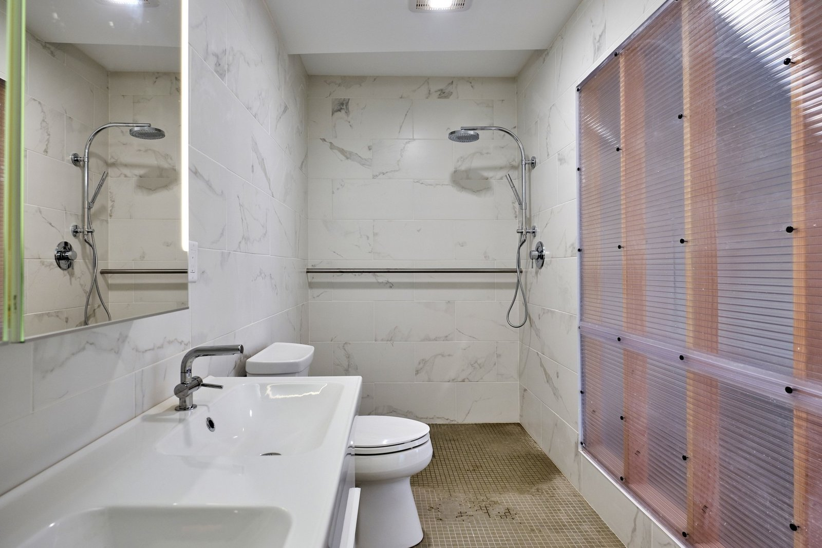 Bath Room, Full Shower, Open Shower, and Marble Wall Floor-to-ceiling marble lines the walls in one of the two full bathrooms.  Photo 8 of 10 in A Connecticut Condo That Hugs the Patchogue River Asks $575K