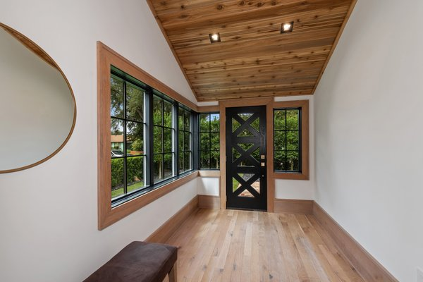New windows wrap around a corner of the entryway. The natural oak flooring and cedar tongue-and-groove ceilings run throughout the interior.