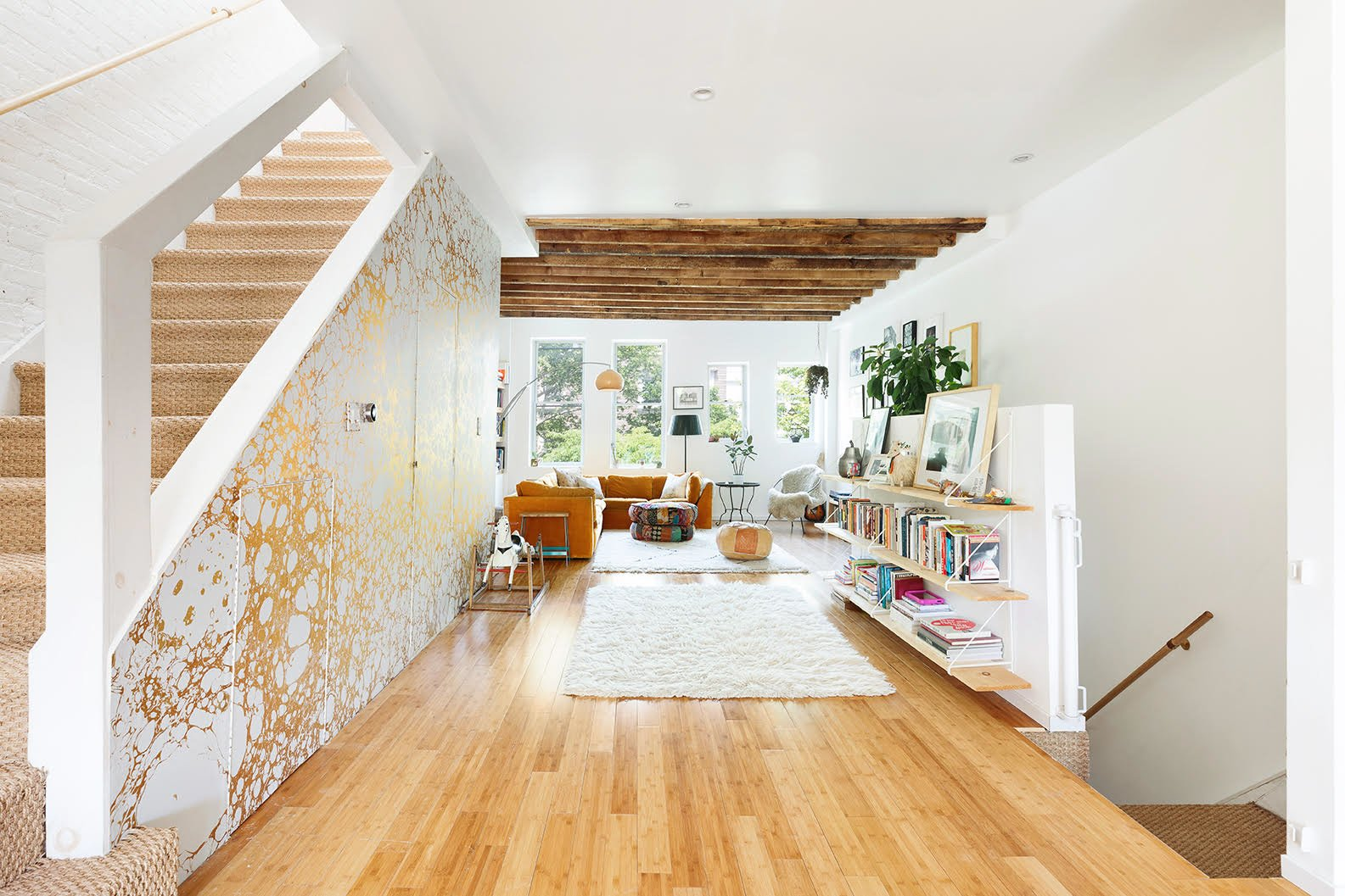 Built in 1905, this Brooklyn townhome underwent a gut renovation that transformed the three-story structure into a bright and airy double duplex. The larger residence occupies the top two floors and features handcrafted, gold-foil wallpaper that contrasts with wooden beams and floors.  Photo 1 of 8 in A Brooklyn Townhouse Reimagined as a Crisp, Loft-Like Duplex Asks $2.75M