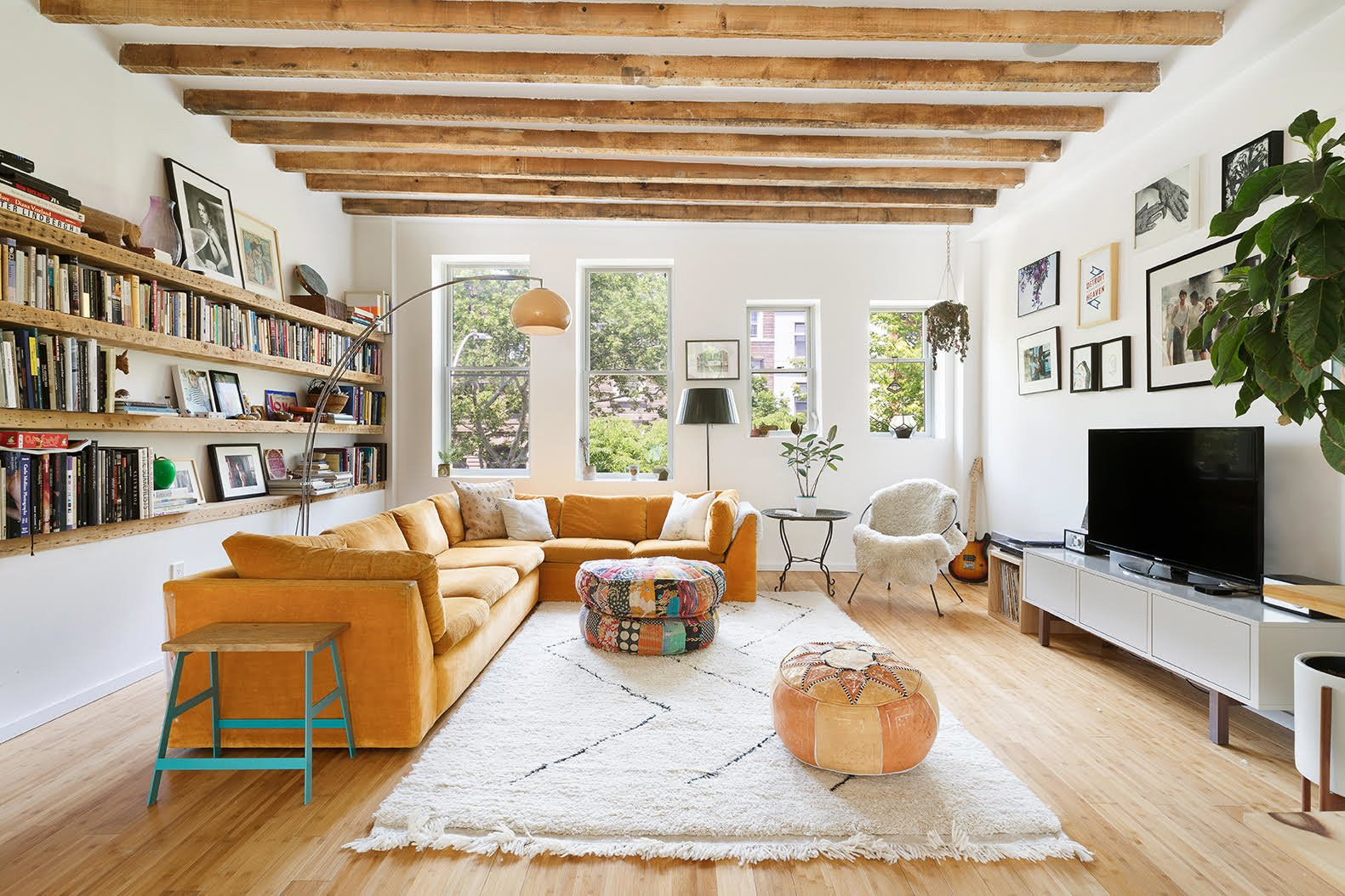The loft-inspired living room features bookshelves made of salvaged wood along one wall. Exposed beams—also salvaged wood—run along the ceiling.  Photo 2 of 8 in A Brooklyn Townhouse Reimagined as a Crisp, Loft-Like Duplex Asks $2.75M