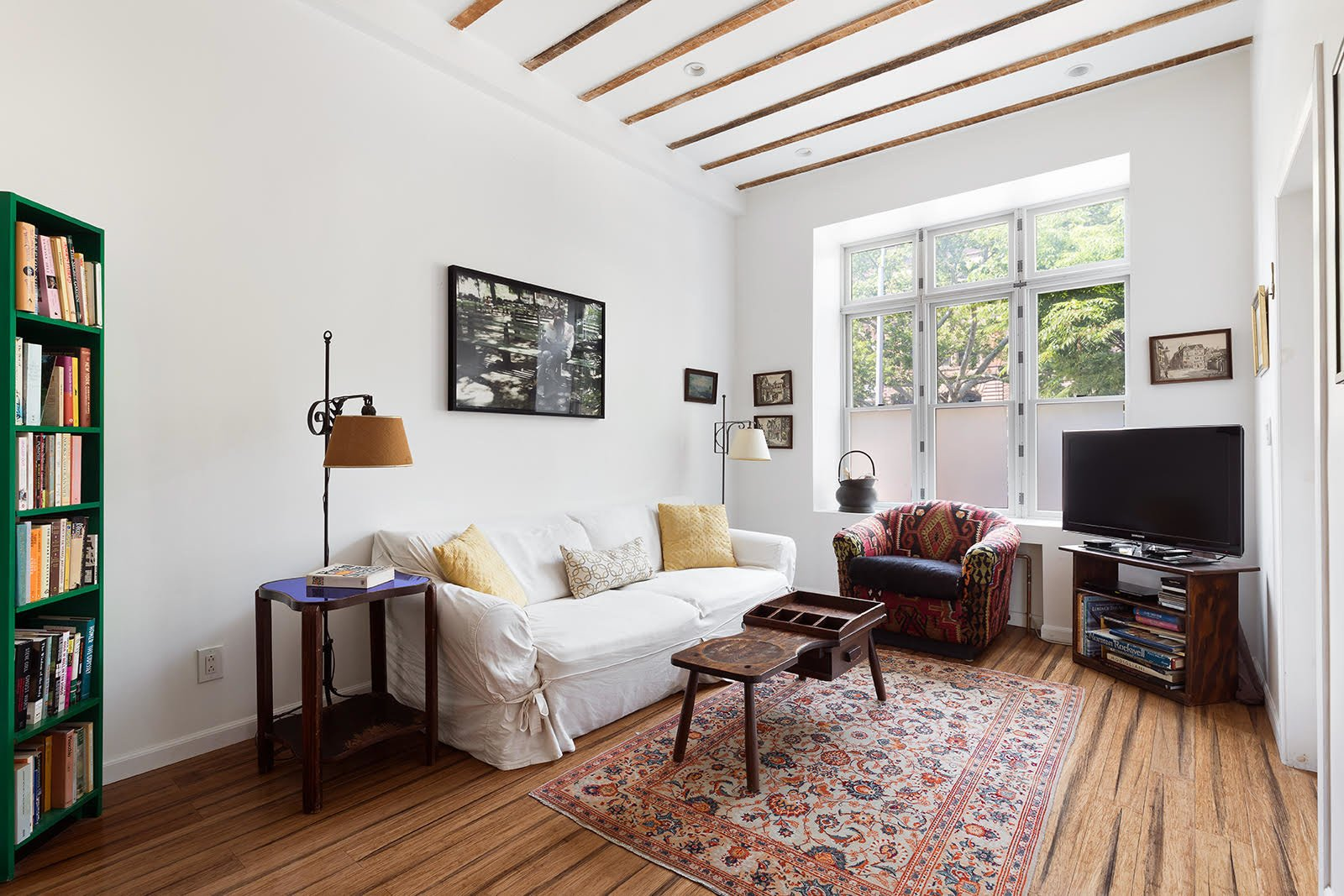 The airy aesthetic continues downstairs to the lower-level unit. Here, a large living area features more wood details contrasted by crisp, white walls.  Photo 6 of 8 in A Brooklyn Townhouse Reimagined as a Crisp, Loft-Like Duplex Asks $2.75M