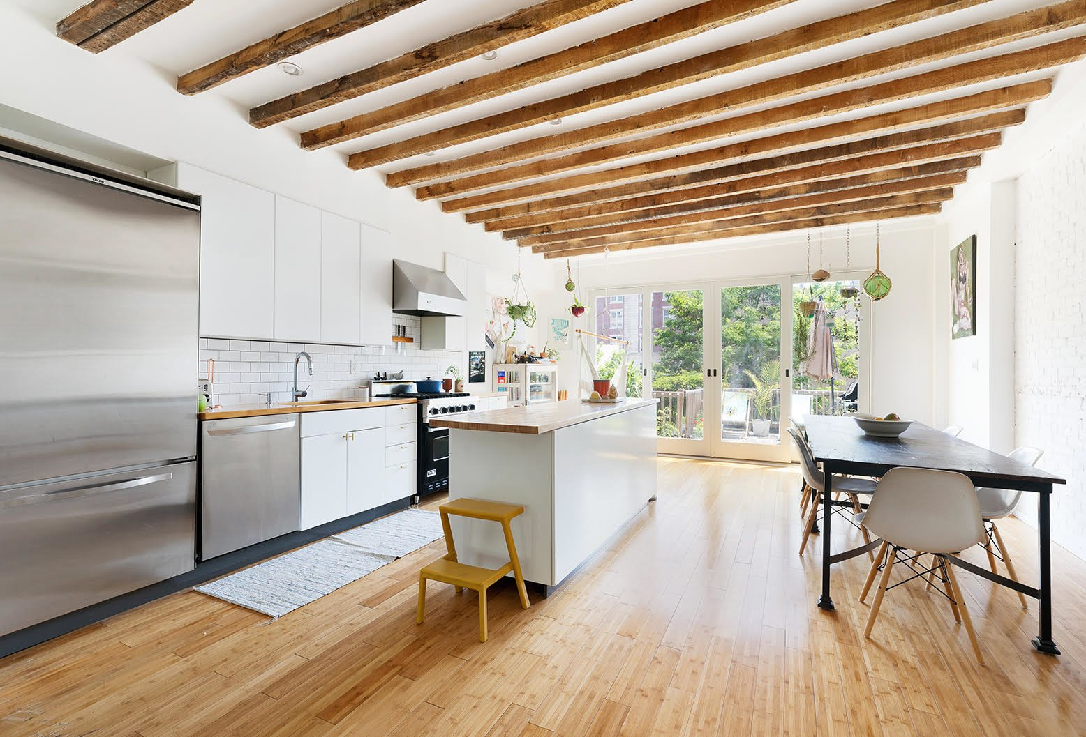 Exposed beams continue into the upper-level kitchen. Sliding glass doors provide natural light and lead out to a private deck.  Photo 3 of 8 in A Brooklyn Townhouse Reimagined as a Crisp, Loft-Like Duplex Asks $2.75M