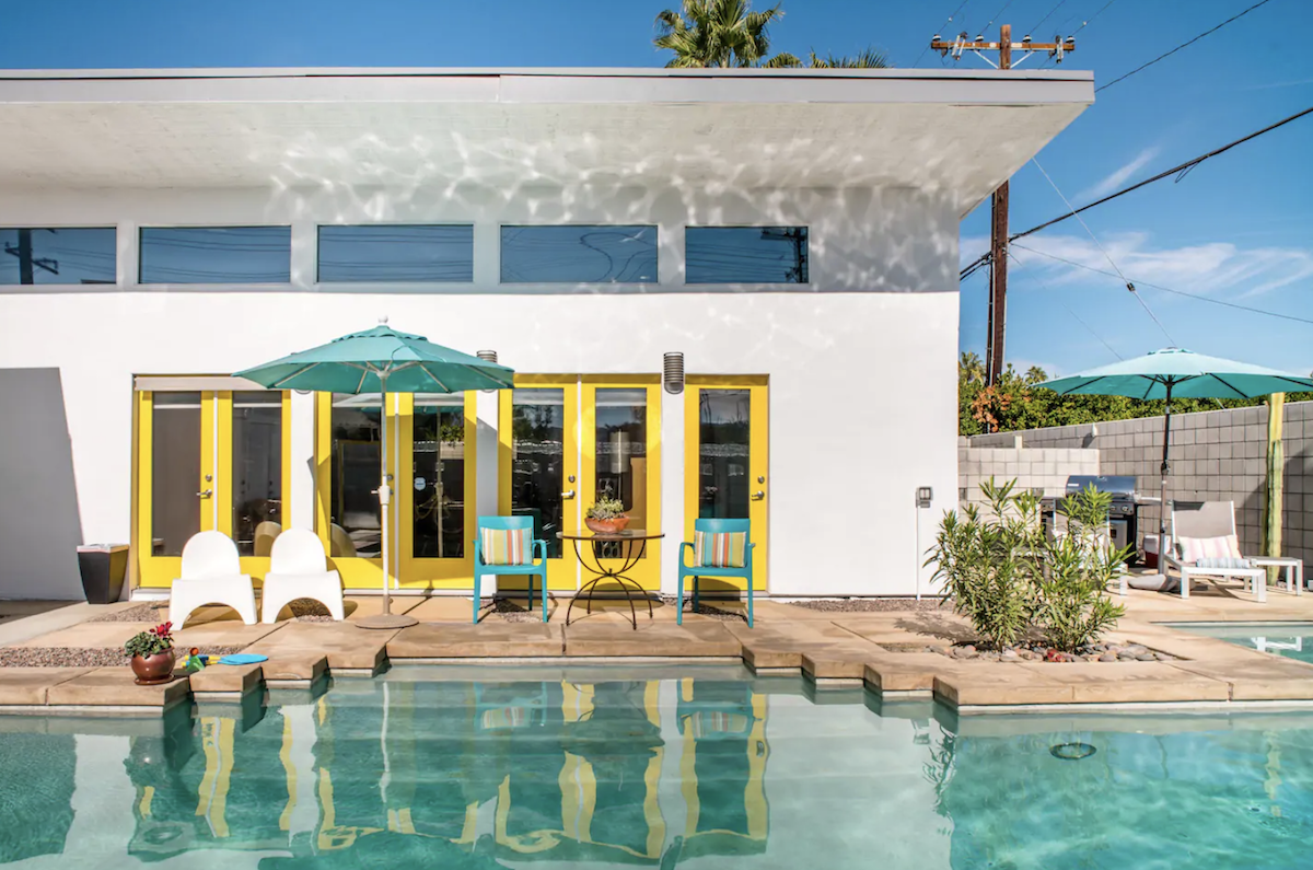 Outdoor, Large Pools, Tubs, Shower, Concrete Fences, Wall, Trees, Back Yard, and Horizontal Fences, Wall The colors of this home are like wrapping paper: bright, cheery and unabashed (even the exterior doors are painted in a striking yellow). Plus, when guests stay at this open one-bedroom, one-bathroom retreat, they'll leave with a custom gift made by a local artist. This rental includes several amenities such as a pool and bicycles for riding into town.  Photo 14 of 15 in 15 Picture-Perfect Airbnbs in Palm Springs Starting at $119 a Night