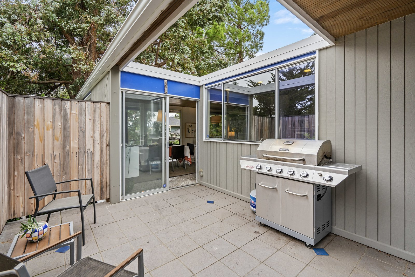 Outdoor, Back Yard, Wood Fences, Wall, Trees, Small Patio, Porch, Deck, and Vertical Fences, Wall Outside, a cutout in the roof hangs over the enclosed patio area.  Photo 8 of 12 in A Case Study–Style Home in San Luis Obispo Lists for $870K