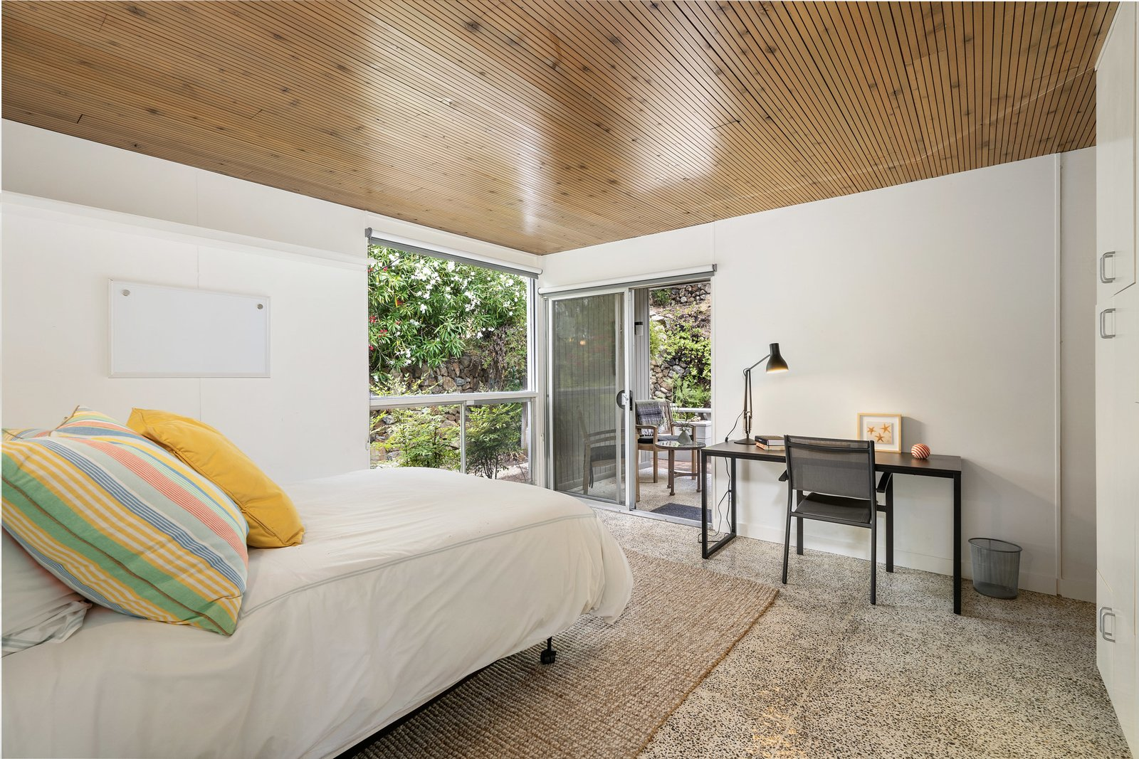 Bedroom, Bed, Chair, and Table Lighting Back inside, each of the two bedrooms offer large windows and private outdoor spaces.  Photo 9 of 12 in A Case Study–Style Home in San Luis Obispo Lists for $870K