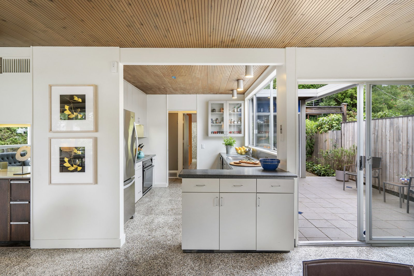 Kitchen, Ceiling Lighting, White Cabinet, Cooktops, and Refrigerator An opposite view from the dining area looks into the kitchen. A small peninsula connects the two spaces while a sliding glass door opens onto a side patio.  Photo 6 of 12 in A Case Study–Style Home in San Luis Obispo Lists for $870K
