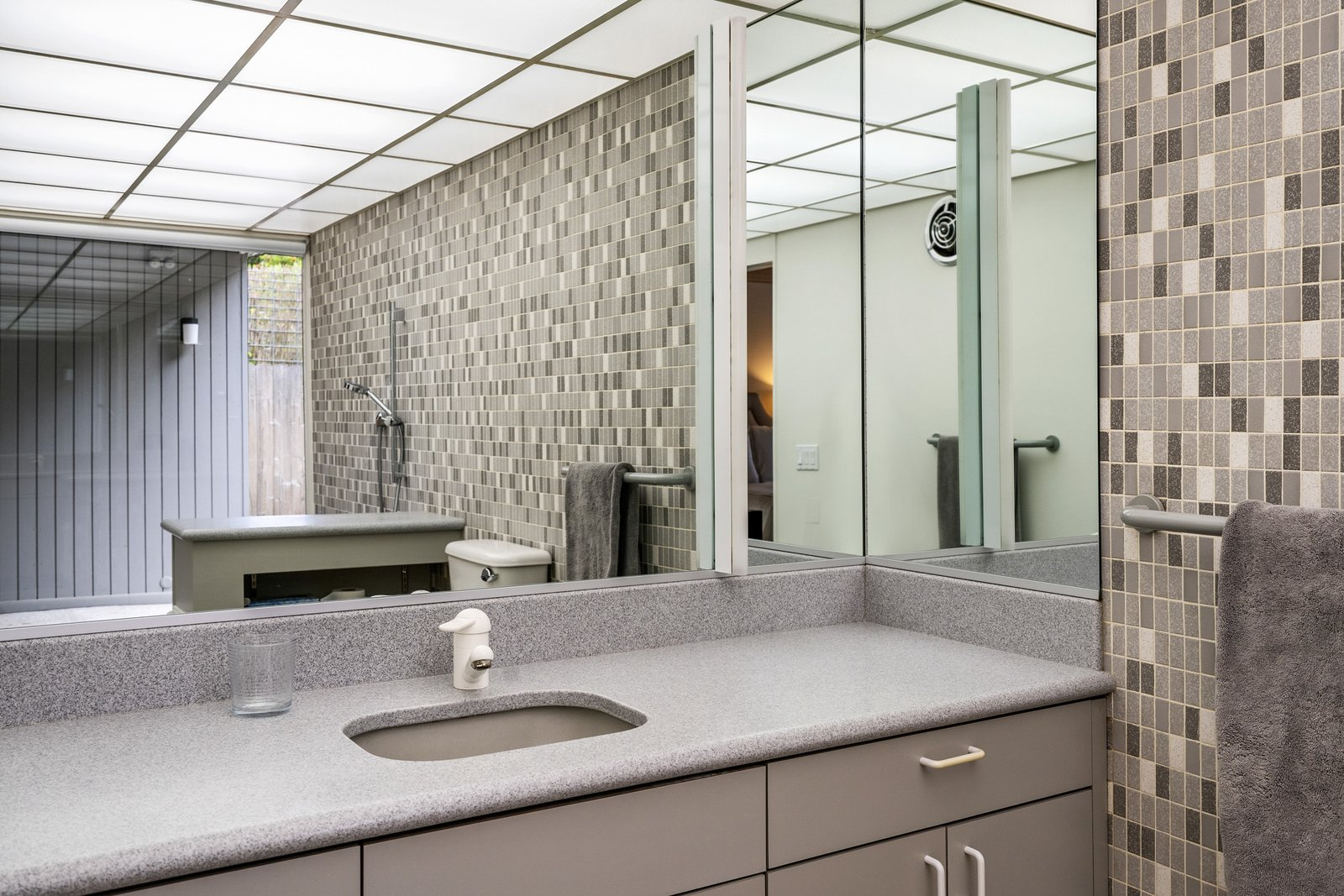 Bath Room, Wall Mount Sink, Ceramic Tile Wall, and Ceiling Lighting A look at the home's bathroom. Mirrors and a wall of glass make the space feel larger.  Photo 10 of 12 in A Case Study–Style Home in San Luis Obispo Lists for $870K