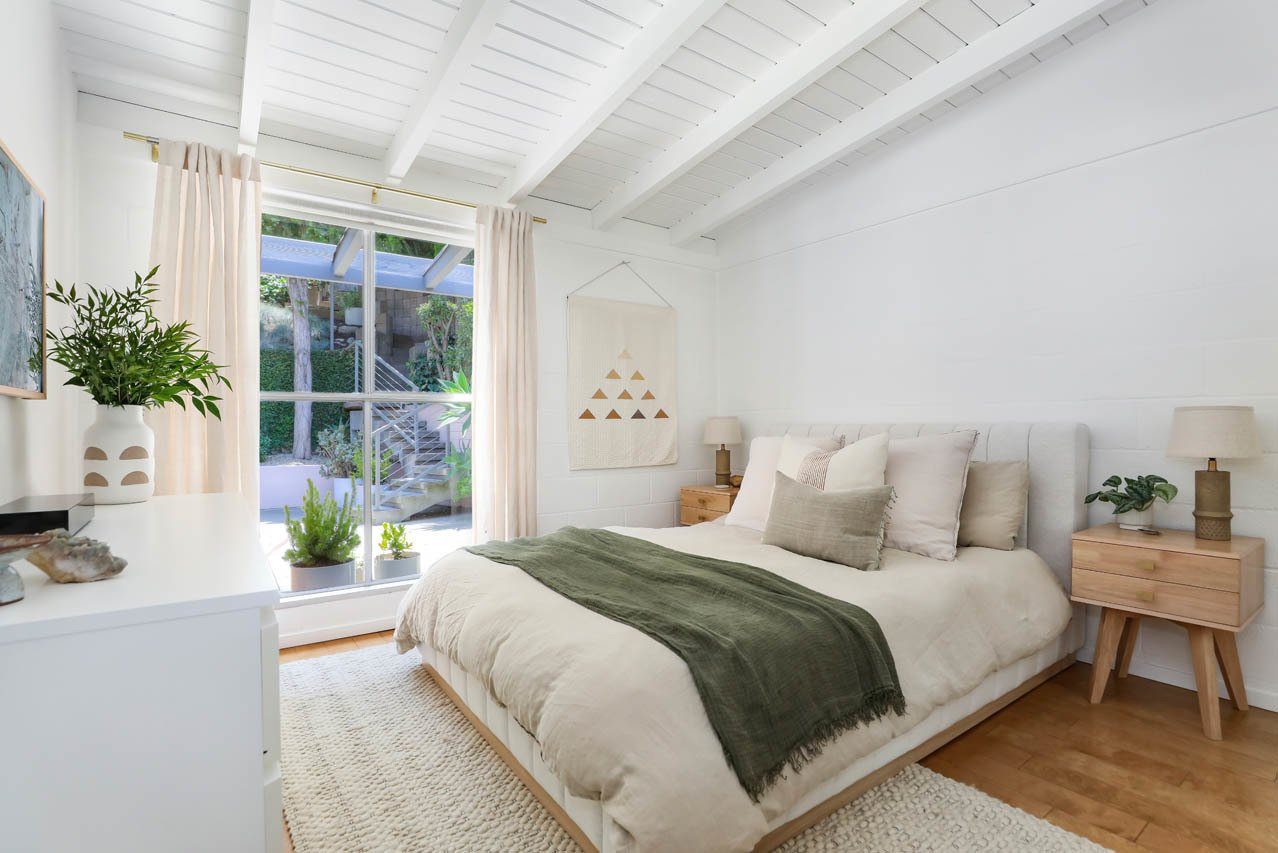 Bedroom, Medium Hardwood Floor, Table Lighting, Dresser, Lamps, Bed, and Night Stands Here is one of the home's two bedrooms.  Photo 9 of 13 in A Light and Bright L.A. Midcentury Renovation Slides Onto the Market for $899K