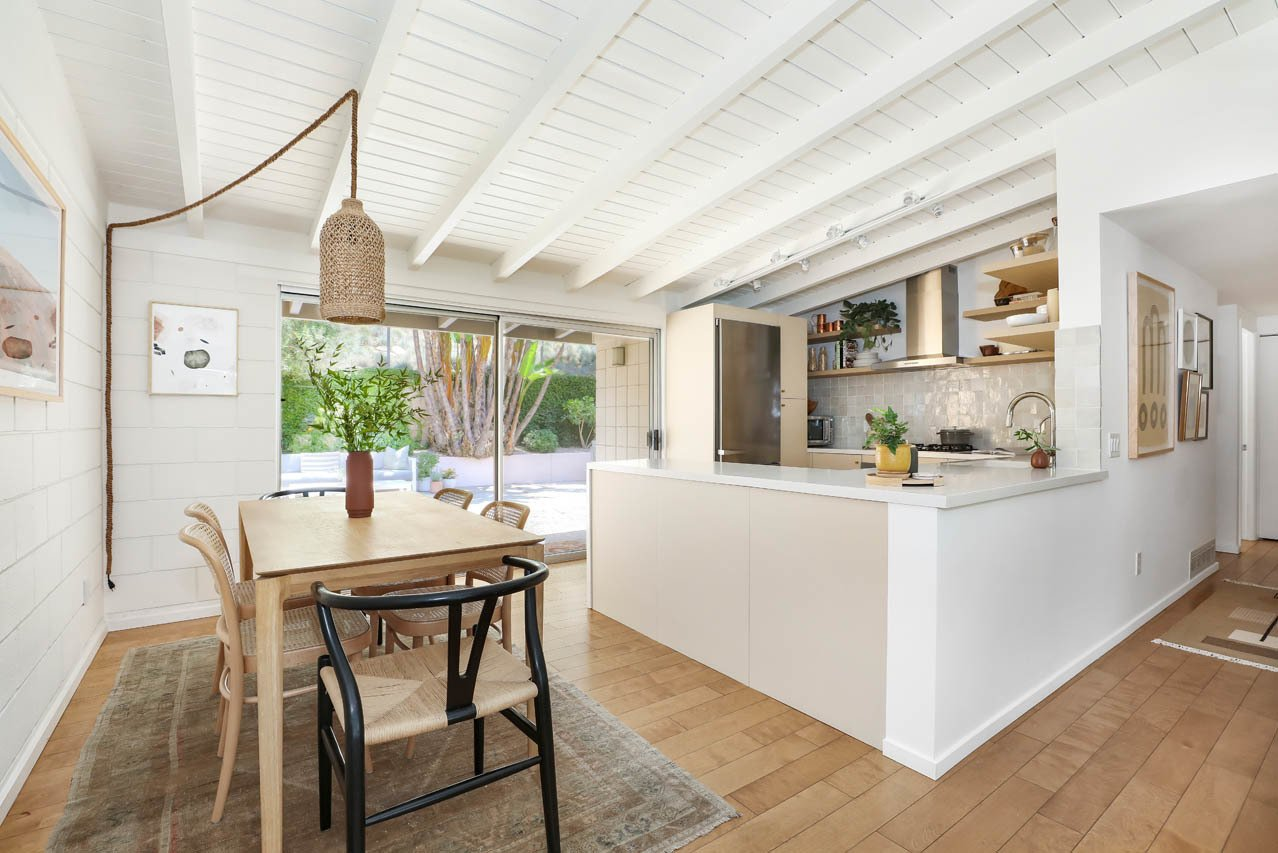 Dining Room, Medium Hardwood Floor, Table, Ceiling Lighting, Chair, and Rug Floor Steps away from the living room is the recently remodeled kitchen, complete with Caesarstone counters, custom cabinetry, and appliances by Miele and Fisher & Paykel.  Photo 6 of 13 in A Light and Bright L.A. Midcentury Renovation Slides Onto the Market for $899K