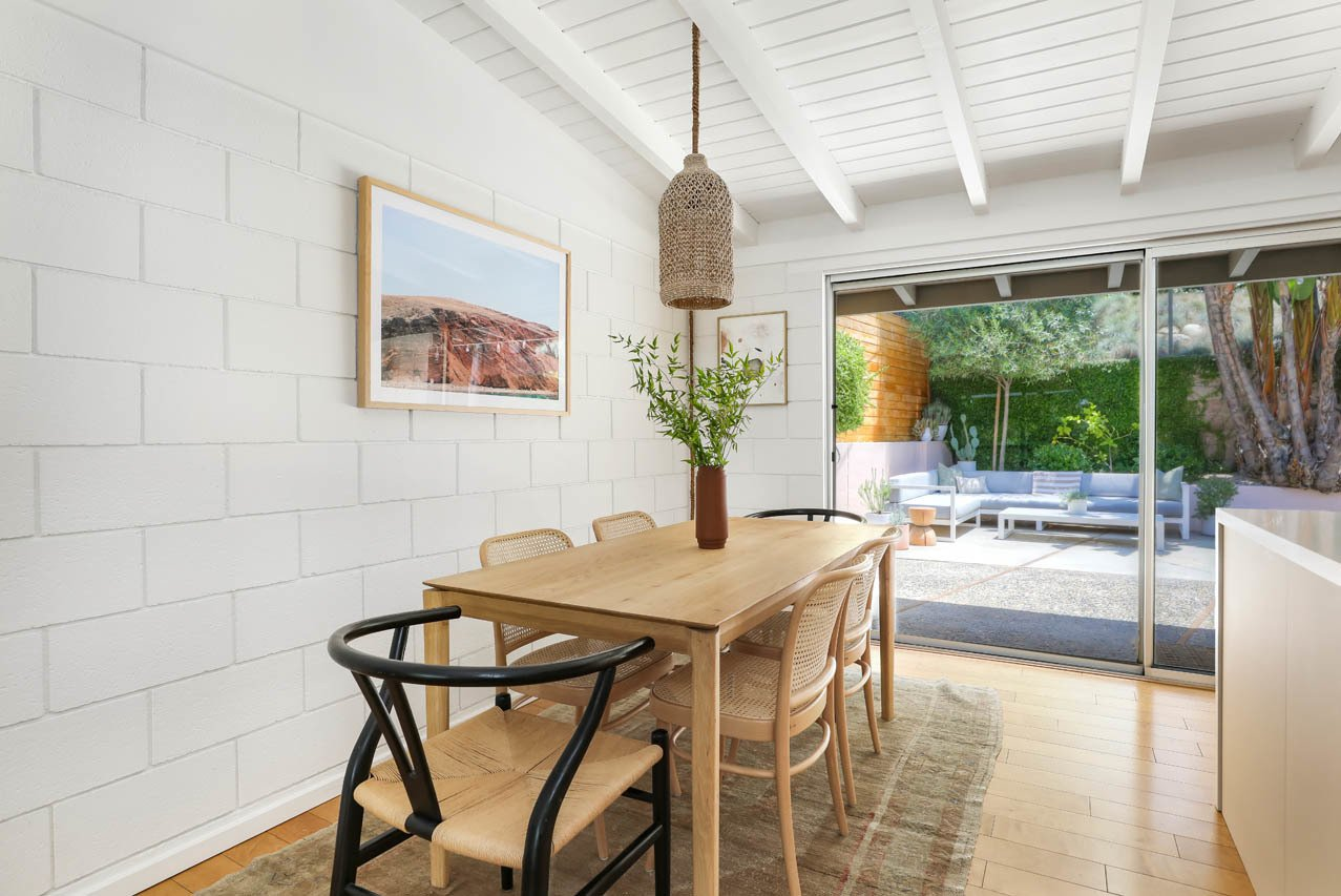 Dining Room, Chair, Table, Medium Hardwood Floor, Ceiling Lighting, and Rug Floor Sliding glass doors create an immediate indoor-outdoor connection, allowing fresh breezes to sweep inside.  Photo 7 of 13 in A Light and Bright L.A. Midcentury Renovation Slides Onto the Market for $899K