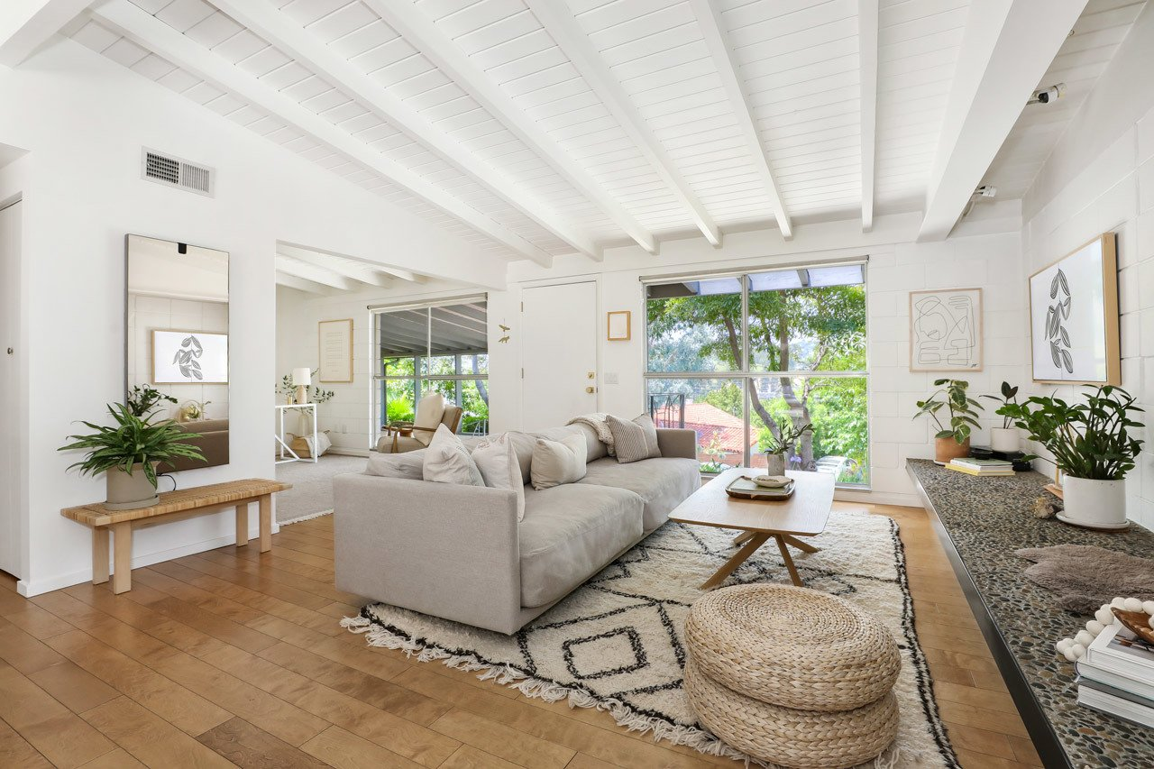 Living Room, Sofa, Ottomans, Bench, Medium Hardwood Floor, and Coffee Tables Another view of the living room which showcases the expansive windows sandwiching the front door. Exposed beams span the ceiling while original hardwoods line the floors.  Photo 4 of 13 in A Light and Bright L.A. Midcentury Renovation Slides Onto the Market for $899K