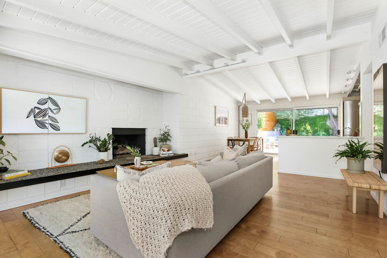 Living Room, Bench, Coffee Tables, Standard Layout Fireplace, Medium Hardwood Floor, and Sofa The main entrance leads into the light-filled living room, where a cinderblock hearth and cast-stone sitting ledge take center stage.  Photo 3 of 13 in A Light and Bright L.A. Midcentury Renovation Slides Onto the Market for $899K
