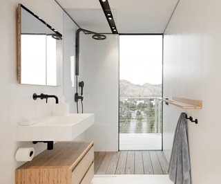 Even the bathroom grants views. Sleek wood elements complement the white-and-black fixtures and details.